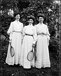 Three young women in light dresses holding tennis racquets (3331846787).jpg