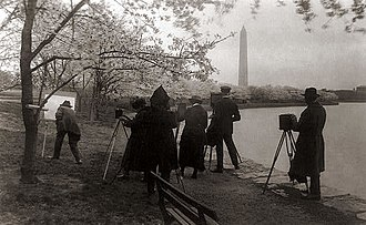 National Cherry Blossom Festival - Photographers and painters along the Tidal Basin under blossoming cherry trees, 1920