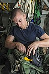 U.S. Navy Aircrew Survival Equipmentman 3rd Class Matthew Sandman assigned to Strike Fighter Squadron (VFA) 147 installs a camelbak pouch into a survival vest aboard the aircraft carrier USS Nimitz (CVN 68) 130607-N-ZG290-008.jpg