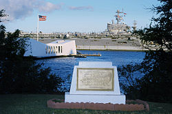 A golden plaque on stone on the shore of Ford Island, with a white memorial bridge floating over the USS Arizona