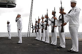 Present arms (command) - Sailors of US Navy present arms during burial on sea on aircraft carrier USS Harry S. Truman.
