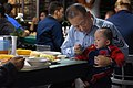 US Navy 071122-N-1805M-061 Storekeeper 1st Class Andy Zhang enjoys Thanksgiving dinner with his 8-month-old son, aboard the Nimitz-class aircraft carrier USS Ronald Reagan (CVN 76).jpg