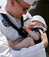 US Navy 080604-N-5345W-303 Aviation Boatswain's Mate (Handling) 3rd Class Nicholas Beyer holds his 4-month-old son for the first time during homecoming celebrations for the crew of the Nimitz-class aircraft carrier USS Harry S.jpg