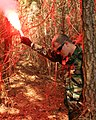 US Navy 100325-M-2550C-038 unner's Mate 2nd Class James Dugan uses a red flare to signal an aircraft for a personnel recovery mission during a training exercise at Marine Corps Auxiliary Landing Field Bogue, North Carolina.jpg
