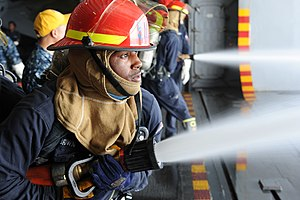 US Navy 120104-N-EK905-047 Electrician's Mate Fireman Emmett Brown trains as number one nozzleman during a general quarters drill in the hangar bay.jpg