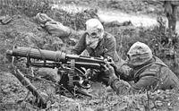 Soldados británicos manejan una ametralladora Vickers provistos de cascos antigás PH con tubos de respiración.