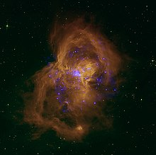 Bright blue stars in a large gold cloud of gas