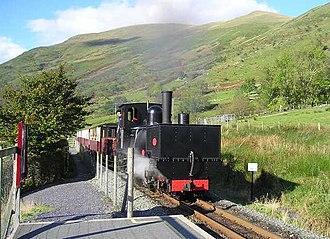 Welsh Highland Railway - WHR locomotive K1, the first Garratt articulated locomotive, at Snowdon Ranger halt with train and Snowdonia behind