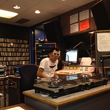 A DJ wearing sunglasses speaks into a microphone, surrounded by audio equipment, a computer, LP players, a darkened glass window, and a soundboard.