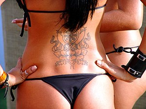 Woman in black thong bikini with tattoo and we...