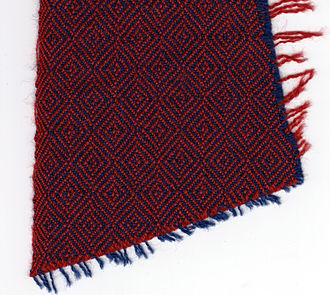 Twill - Diamond twill, with weaving edge (left), blue warp, red weft