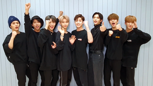 The eight members of Stray Kids, all in black, look forward
