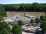 A muddy river floods a wooded urban area with boat docks and riverside seating.