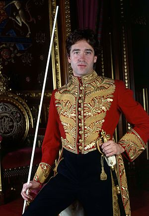 David Cholmondeley, 7th Marquess of Cholmondeley - Cholmondeley at the Palace of Westminster in 1992, wearing the ceremonial dress of Lord Great Chamberlain and holding a white staff of office, borne by certain senior officers of the Royal Household