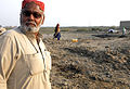 A man stands in front of where his house used to be, Sindh, December 2010 (5331018354).jpg