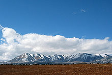 Snow covered mountains protruding from a plain with tilled soil in the foreground.