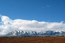 montagne coperte di neve che sporgono da una pianura con terreno lavorato in primo piano.