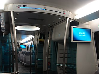 Airport Express (MTR) - Inside the Airport Express with the Entry/Exit Path, along with the Baggage Compartments. The journey status can be seen above the compartment view. The interior has since been updated, with a new indigo carpet and the grey seats replaced with purple seats.