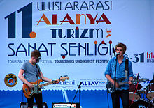 Two guitarists in blue shirts perform on stage in front of a blue and white poster in Turkish.