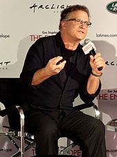 A man wearing a black shirt and trousers, sitting on a chair and talking through a microphone.