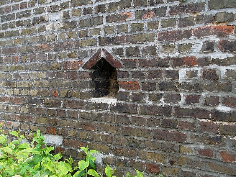 Amiens (Somme, France) - Niche de mitoyenneté dans une propriété (dans l'ancienne cour d'un artisan ou entrepreneur) dans le quartier St-Roch. On remarque bien le sommet de la niche, avec ses 2 briques disposées en bâtière. La partie inférieure (épaisseur de mortier) n'est pas d'origine.  Le mur disposait de 2 niches, à même hauteur. L'autre a été obstruée entre 1995 et 2000 lors de petits travaux de rejointoiement.   Camera location  49°53′29.17″N, 2°17′04.56″E  View this and other nearby images on: OpenStreetMap - Google Earth    49.891435;    2.284601