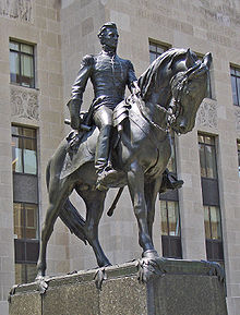 Statue of a man on a horse in front of a large stone building