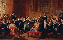 A painting of the Westminster Assembly in session. Philip Nye is standing and gesturing. Various figures are seated around a table. Prolocutor William Twisse is seated on a raised platform.