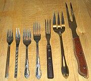 Assorted forks. From left to right: dessert fork, relish fork, salad fork, dinner fork, cold cuts fork, serving fork, carving fork.