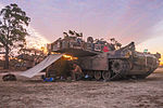 Australian Soldiers from the 1st Armored Regiment take cover for the night under a M1A1 Abrams in 2015.jpg
