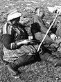 Båndfletting. En kvinne sitter ved siden av en mann og fletter bånd. Lyngen, Troms 1947 - Norsk folkemuseum - NF.13712-012.jpg