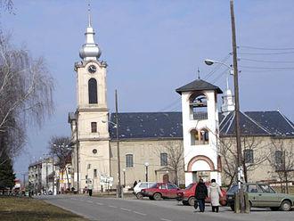Bajmok - Street in Bajmok, the Catholic Church (right), and bell-tower of the Orthodox church (left)