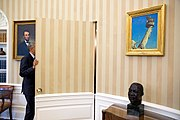 Barack Obama framed by a bust of Martin Luther King Jr. and a painting of Abraham Lincoln