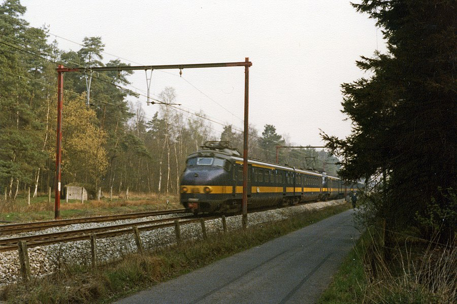 Three Benelux electric units between Kapellen and Kapellenbos in Belgium on line 12. The sideroad is limited traffic and no through road for cars. However it is fully used as a bike route.