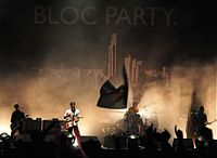 "Two guitarists, a drummer, and a bassist are performing on a smoky stage lit by white stage lights. The stage background is a black tarpaulin emblazoned with ""BLOC PARTY."" and a large black-and-white cityscape below it. Most of the crowd have their hands up in the foreground, which also includes a waving flag."