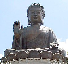 large bronze statue of Buddha with right hand raised