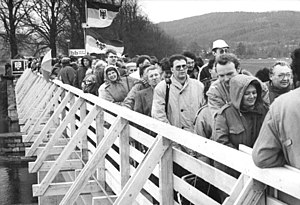 Fall of the inner German border - A new border crossing for pedestrians across the Inner German border linking Lauchröden in Gerstungen municipality, and Herleshausen. This temporary bridge was built immediately after the reopening of the border at the site of an old bridge across the Werra which was destroyed in the Second World War. Here, visitors are queueing to enter East Germany on 23 December 1989.