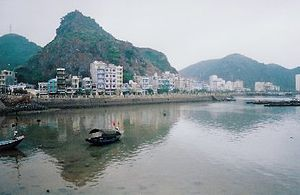 Cát Bà Island - Cat Ba town, showing the limestone hills behind the waterfront strip