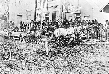 Front Street in Dawson with wagon stuck in mud, 1898