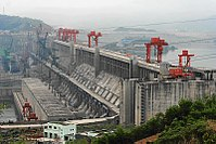 Aerial view of a huge concrete structure located between the mountains, with buildings, power lines and construction and lifting cranes