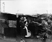 Black and white photograph of a woman wearing traditional Japanese clothing holding a small child while standing in front of a crudely built shack. Rubble and undamaged houses are visible in the background.
