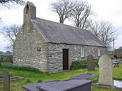 A small plain stone church seen from an angle with a bellcote on the near gable, and a simple door and two windows along the side