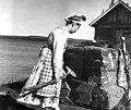 En kvinne foran bakerovn utenfor en bygning. Kirakka järvi 1959 - Norsk folkemuseum - NF.06209-002.jpg