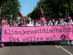 [Foto: Pinker Finger von Ende Gelände 2019: Demonstrierende mit Transparent mit Aufschrift: Klimajereschtischkeit – Dat wollen wa!]