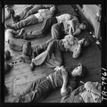 Enlisted men, exhausted after more than 24 hours at general quarters, sleep in tangled patterns aboard the USS... - NARA - 520905.tif