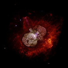 Hubble Space Telescope image showing Eta Carinae and the bipolar Homunculus Nebula which surrounds the star. The Homunculus was partly created in an eruption of Eta Carinae, the light from which reached Earth in 1843. Eta Carinae itself appears as the white patch near the center of the image, where the 2 lobes of the Homunculus touch.
