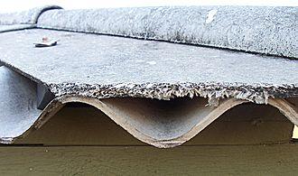 Asbestos abatement - Weathered fibrous asbestos sheeting showing loose fibres
