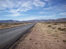 FM 1523, a two-lane road, traverses westward through a Chihuahuan Desert valley toward the Sierra Vieja.