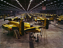 Interior of huge aircraft factory where rows of bombers covered in a yellow layer are manufactured.
