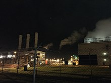 Image shows a gas turbine power station at night.