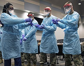 Florida National Guard soldiers collaborate with hospital staff to don personal protective equipment